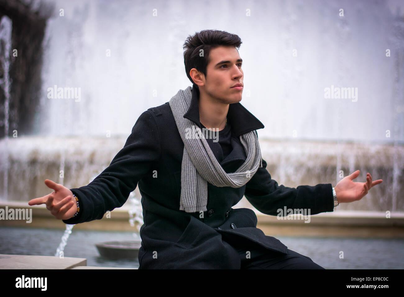 Jeune homme à l'extérieur assis près d'une grande fontaine, avec les bras ouverts et sûrs d'expression propagation Banque D'Images