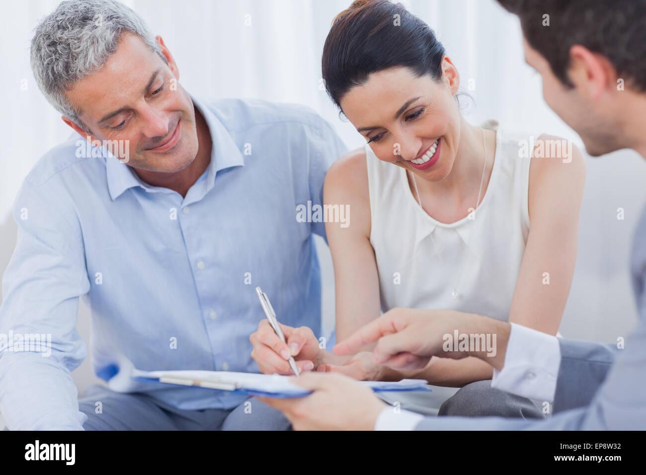 Smiling woman signe sur un contrat de partenariat avec elle sur canapé Photo Stock
