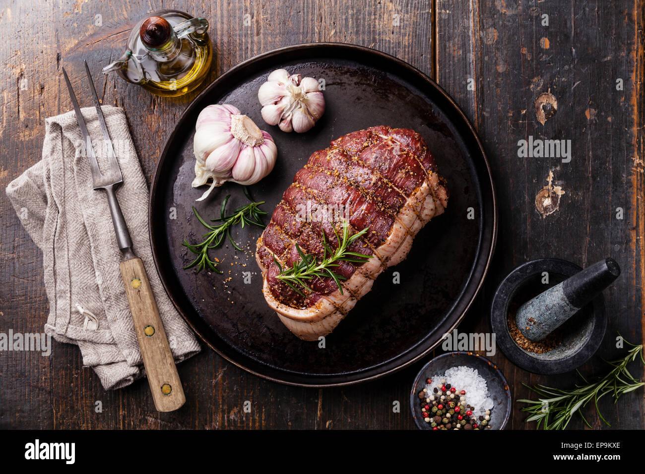 Rôti de bœuf cru Rump, assaisonnements et fourchette à viande sur fond de bois foncé Photo Stock