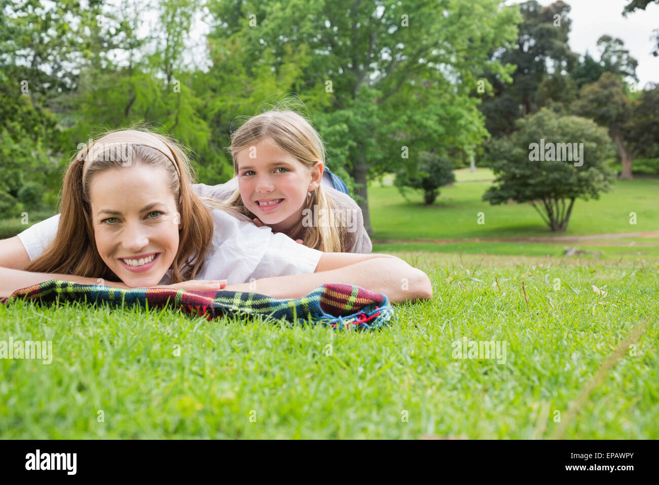 Happy mother with daughter lying at park Photo Stock