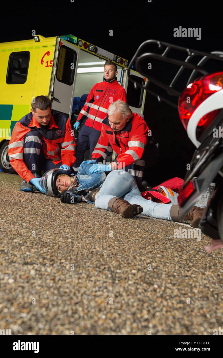 L'équipe d'urgence aider les blessés pilote moto Photo Stock
