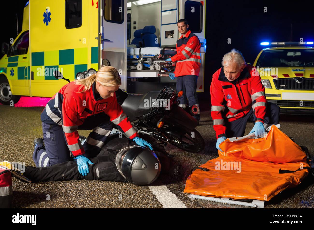 L'équipe d'urgence assistance aux blessés pilote moto Photo Stock