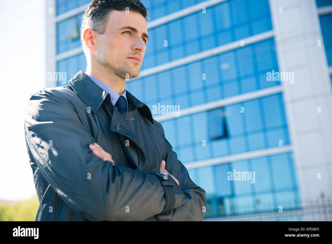 Portrait d'un confident businessman standing with arms folded extérieur. Bâtiment de verre sur fond Photo Stock