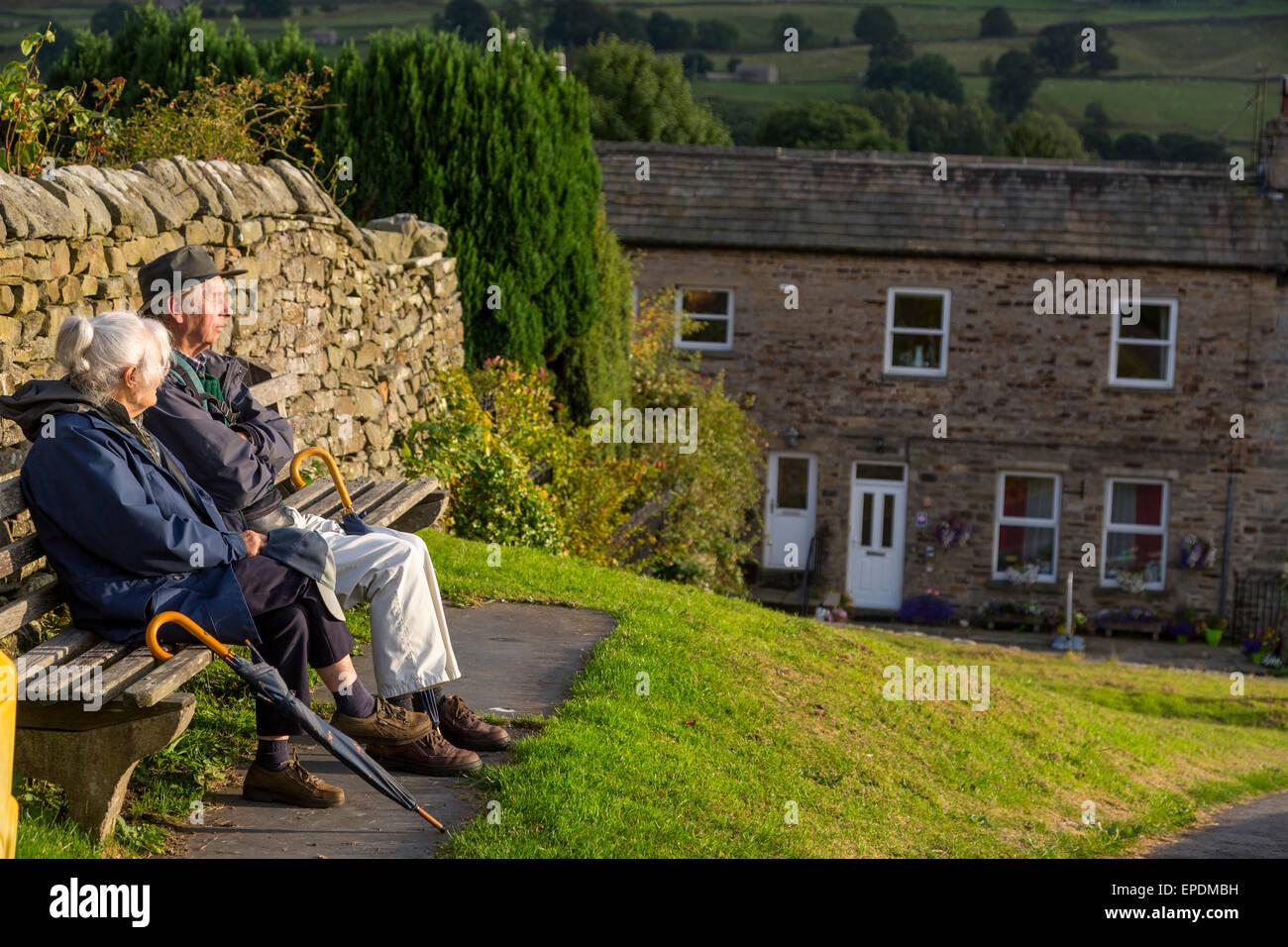 Royaume-uni, Angleterre, dans le Yorkshire, Reeth. Couple de personnes âgées se détendre sur un banc, Photo Stock