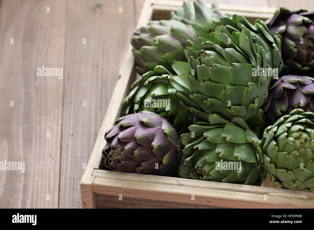 Artichauts en boîte en bois isolé sur fond de bois Photo Stock