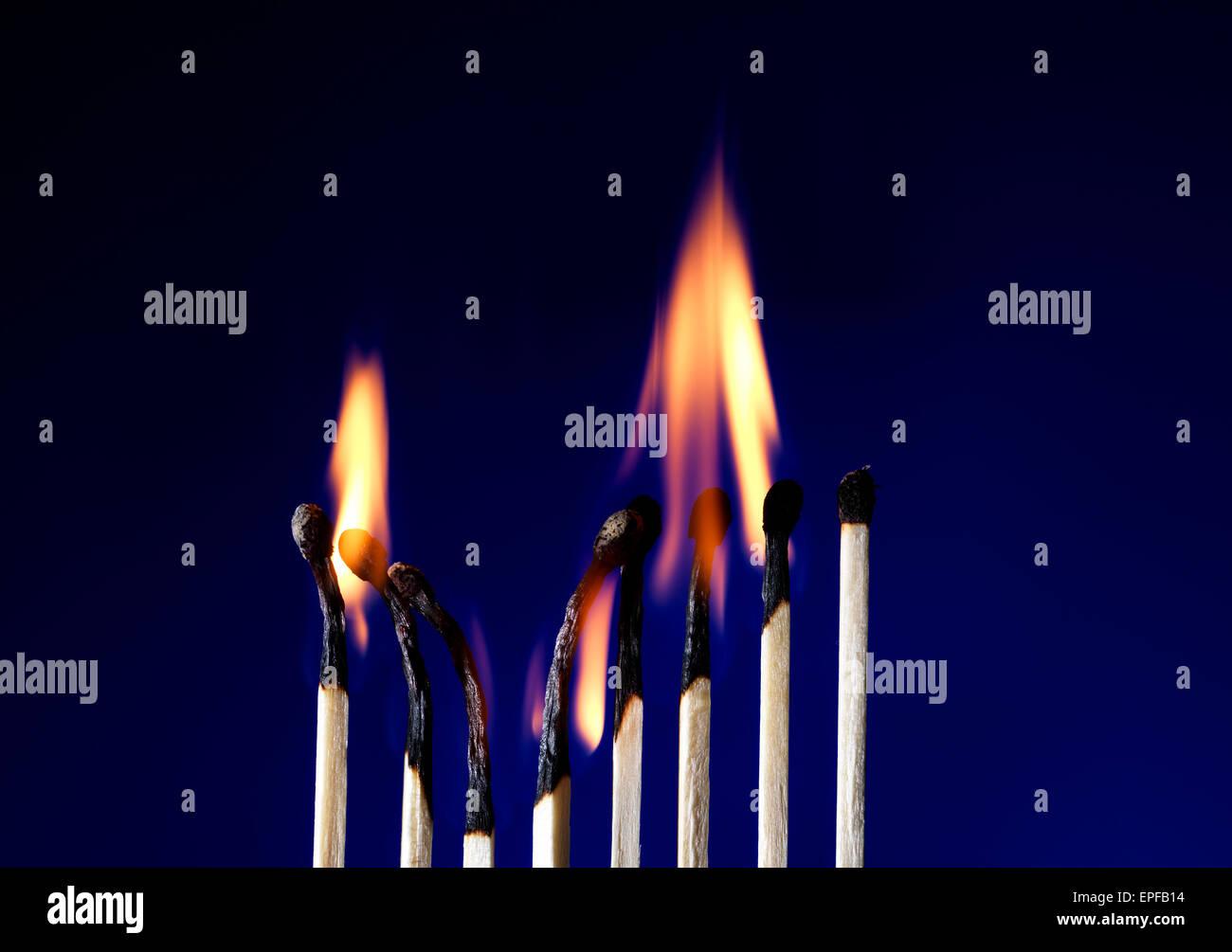 Plan macro sur une allumette enflammée sur bleu Photo Stock