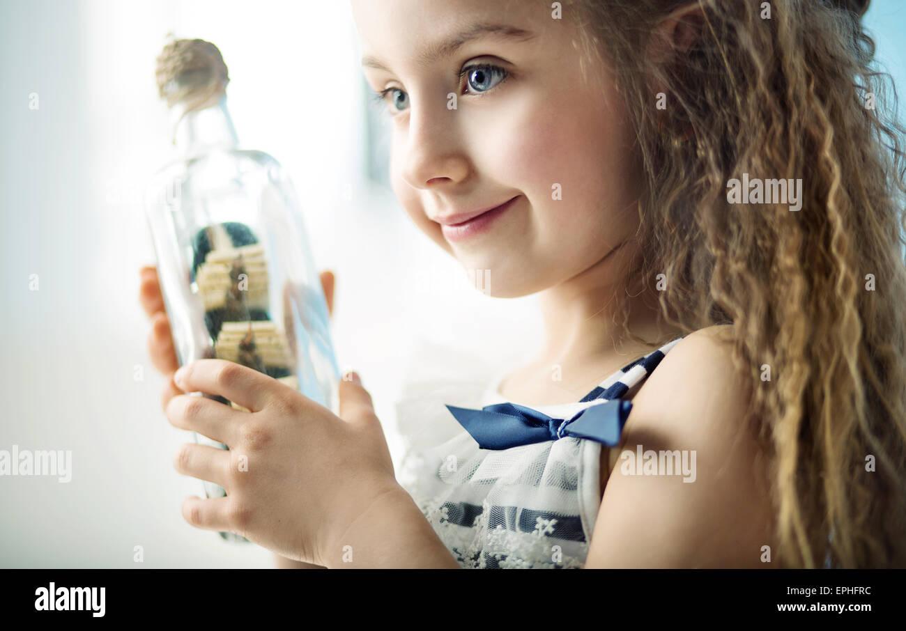 Petit enfant tenant une bouteille avec un navire Photo Stock