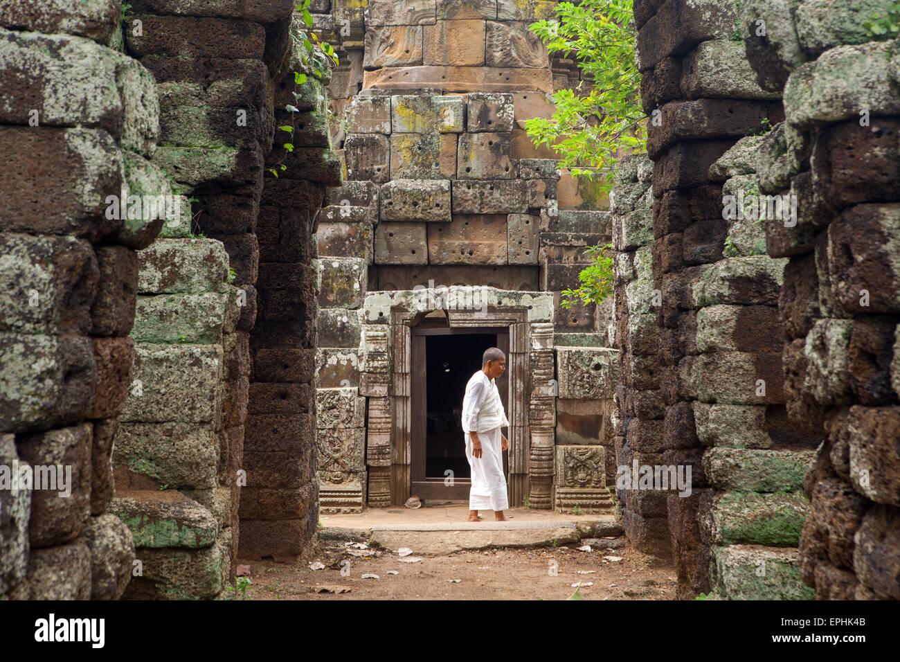 Moine femelle passe entre les portes et les murs de Banteay Prei Nokor à Kompong Cham, au Cambodge. Photo Stock