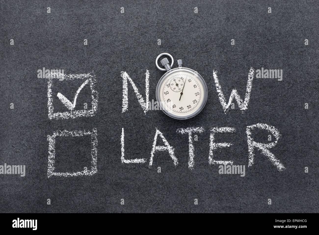 Concept maintenant ou plus tard à la main sur tableau avec vintage chronomètre précis utilisé Photo Stock