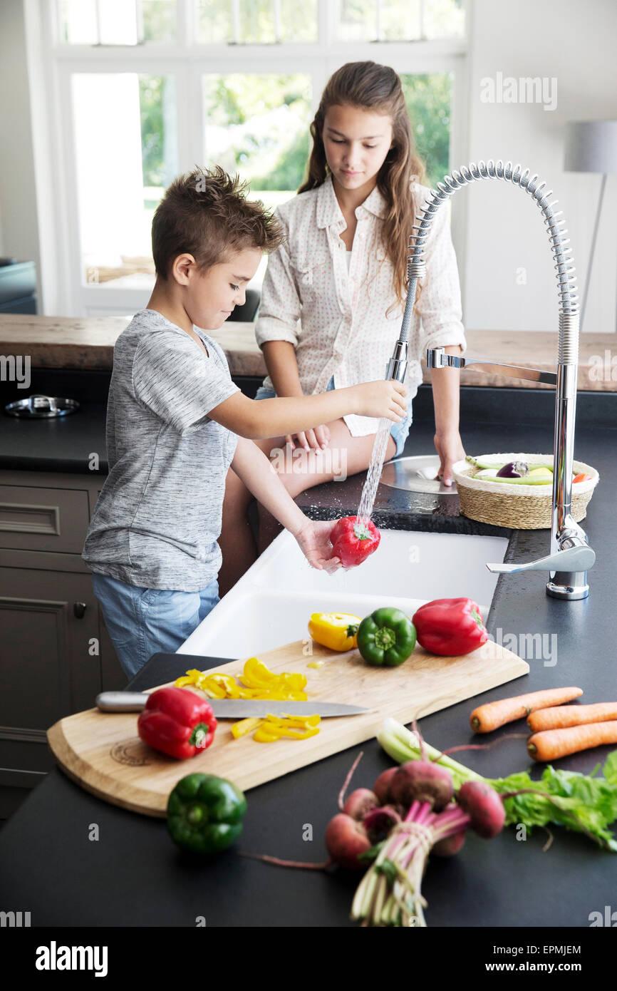 Frère et soeur laver les légumes dans la cuisine Banque D'Images