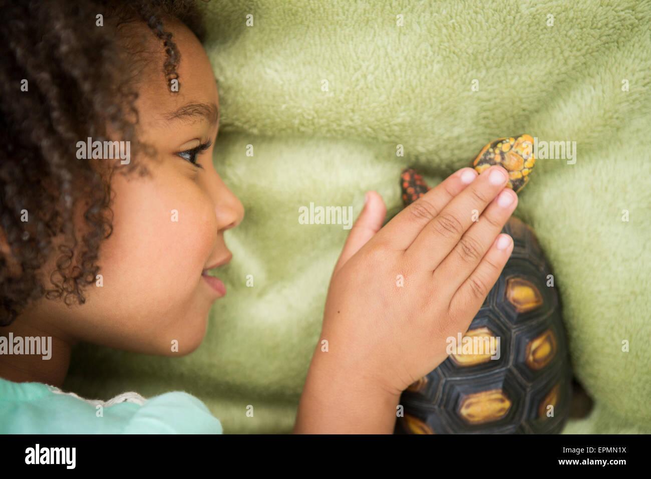 Une jeune fille à la recherche de près une tortue. Photo Stock