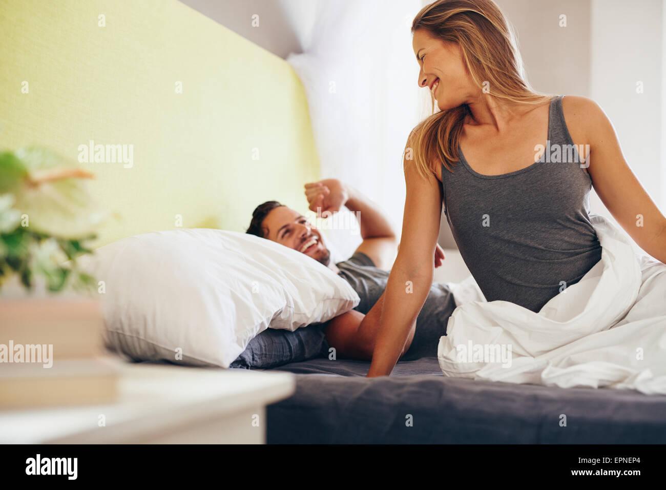 Happy young couple se réveiller le matin au lit. Man and Woman looking at les uns les autres en souriant. Banque D'Images