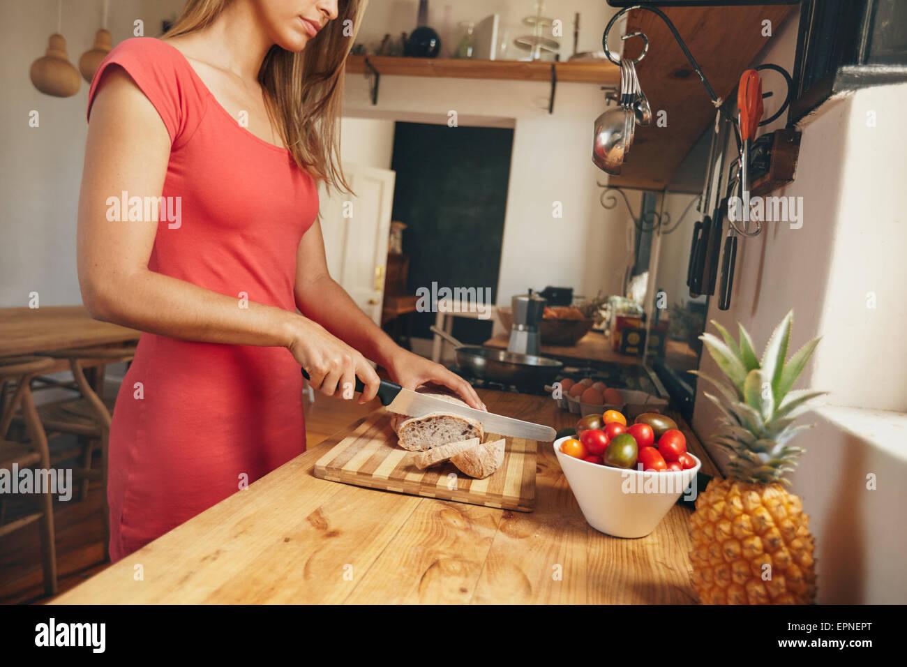 Cropped shot of a young woman slicing une miche de pain frais cuit sur un comptoir de cuisine domestique. Le petit Photo Stock