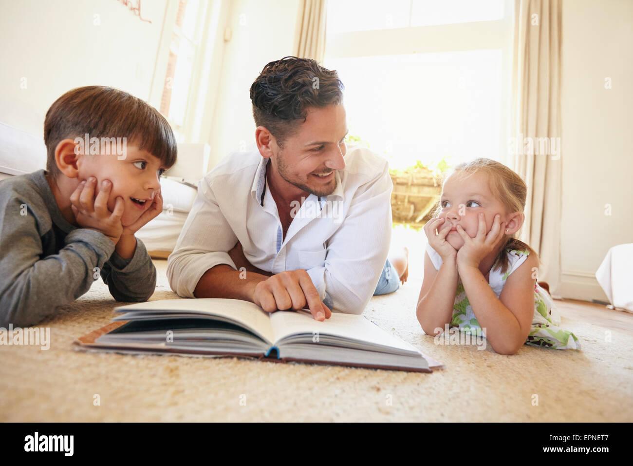 Tourné à l'intérieur du jeune homme avec deux enfants lisant un livre d'histoires. Famille Photo Stock