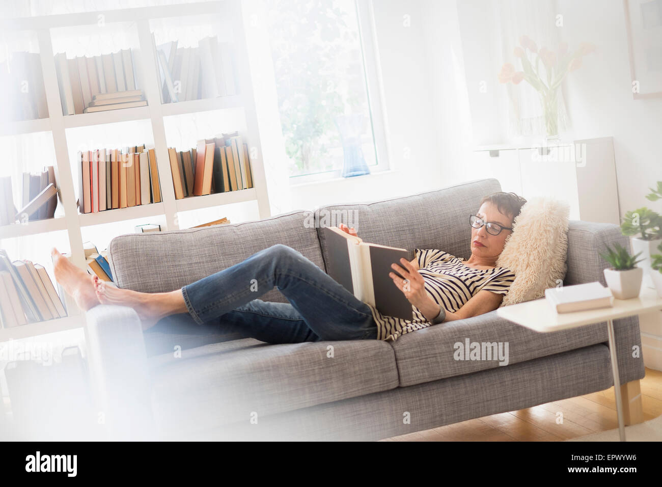 Senior woman reading book on sofa Banque D'Images