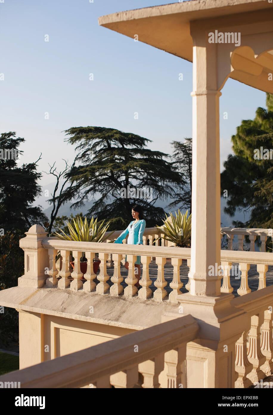 Une jeune femme se tient sur le balcon à l'extérieur de la suite vice-royal à Ananda dans l'Himalaya, Photo Stock