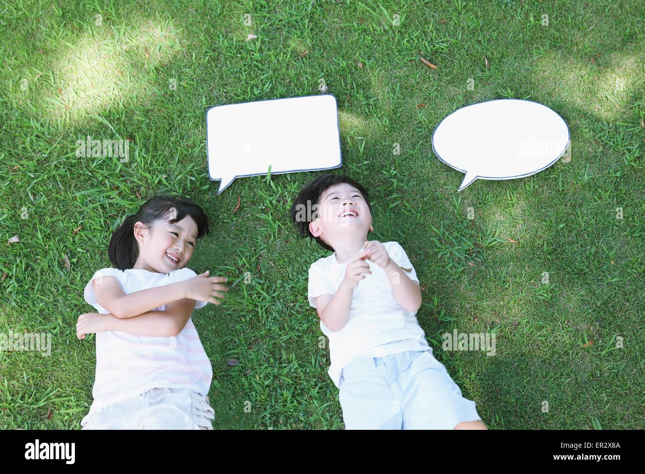 Heureux les enfants japonais pose de tableaux blancs dans un parc de la ville Banque D'Images
