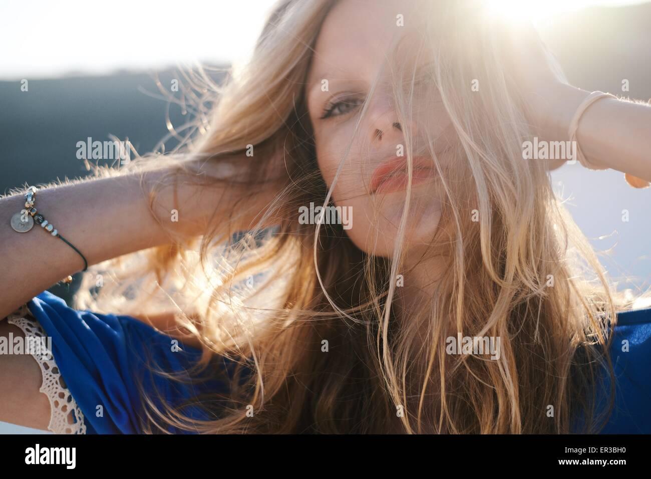 Femme en marche ses mains dans ses cheveux Photo Stock