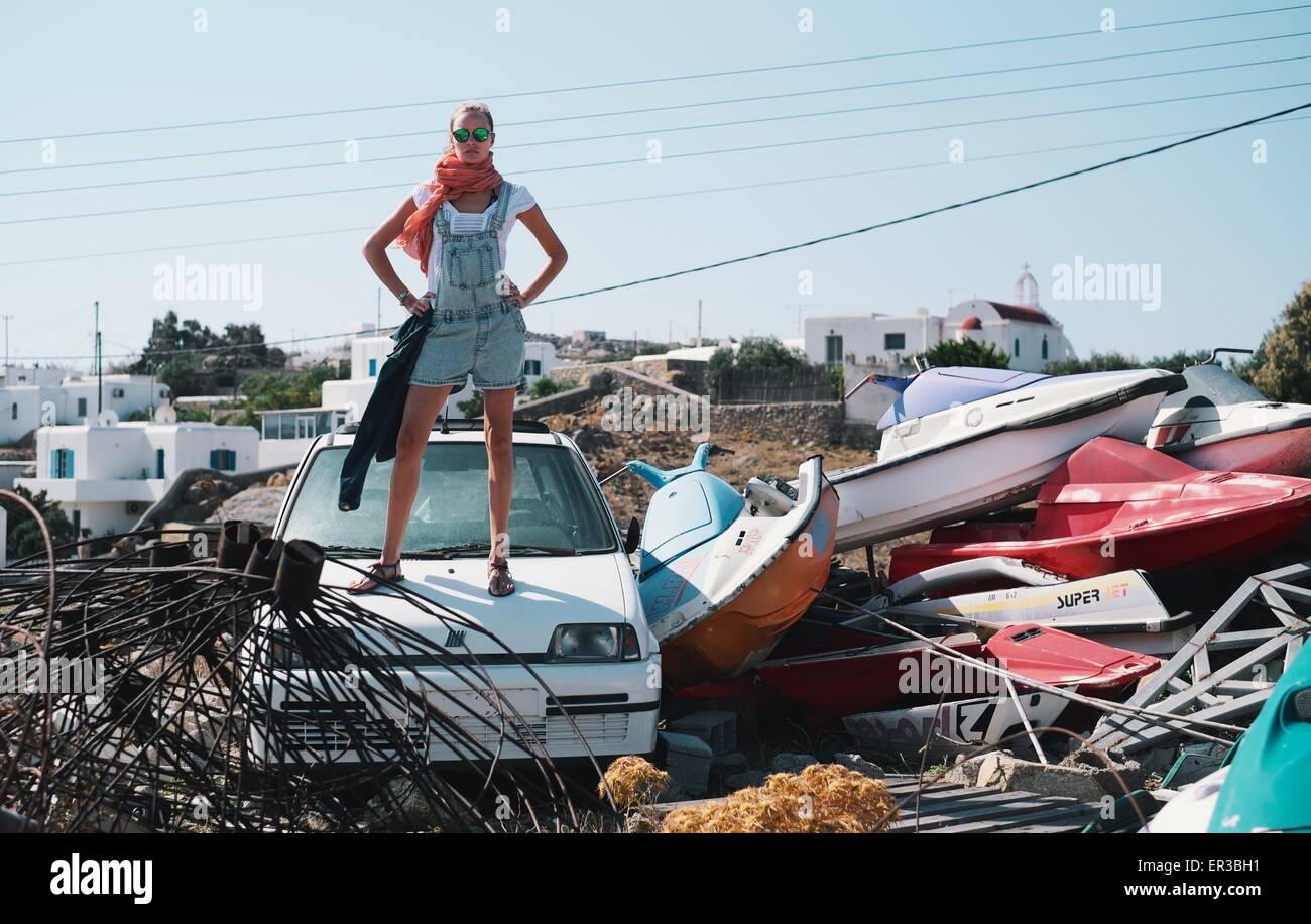 Femme debout sur la voiture en parc à ferrailles Photo Stock