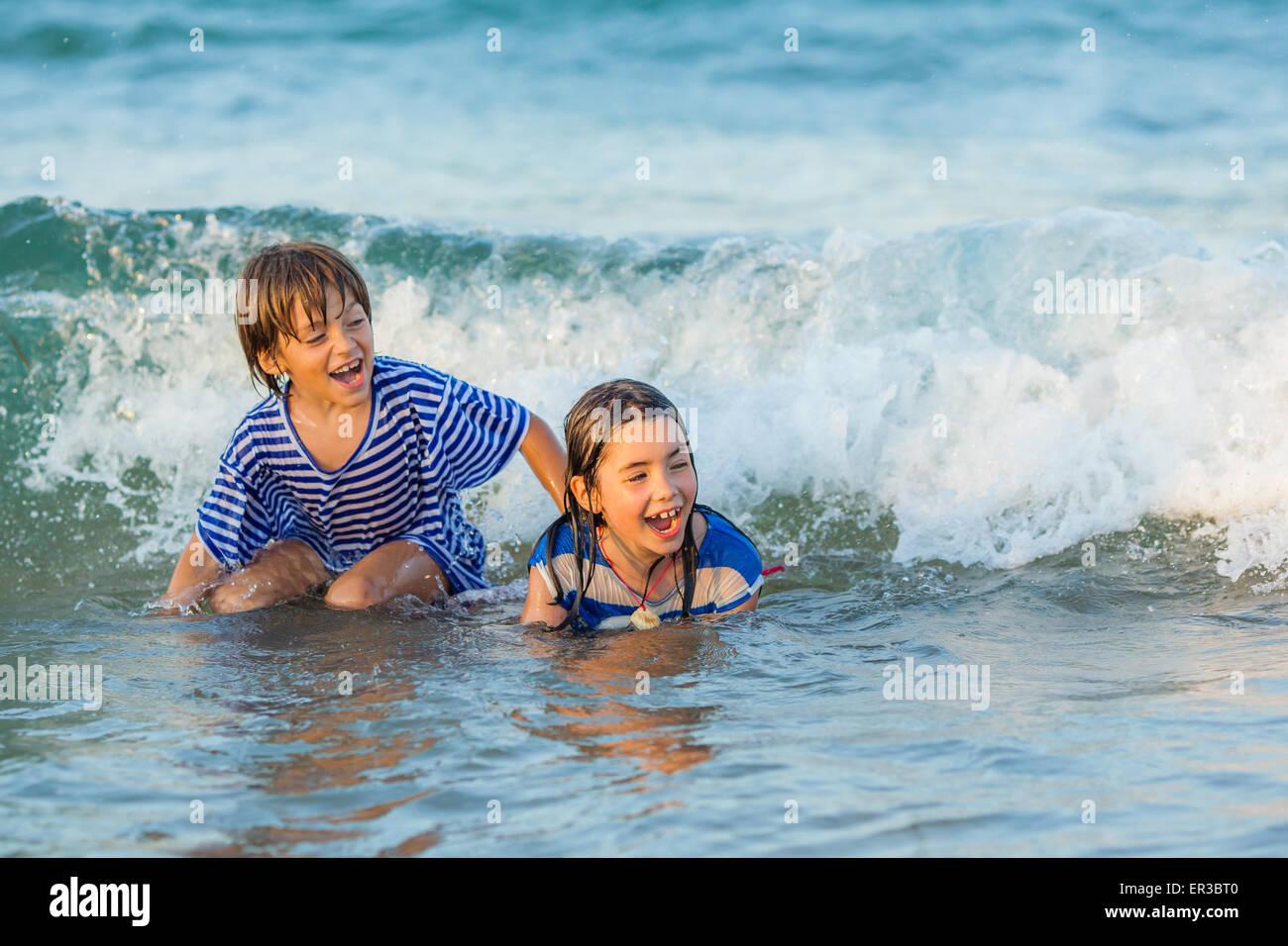 Deux enfants jouant dans la mer Photo Stock