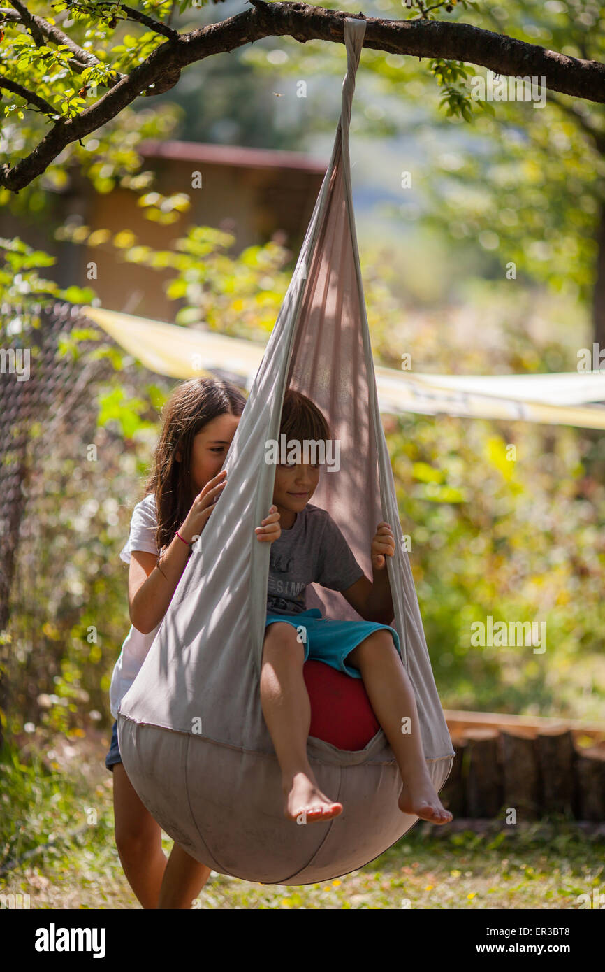 Fille en poussant un garçon sur une balançoire dans le jardin Photo Stock