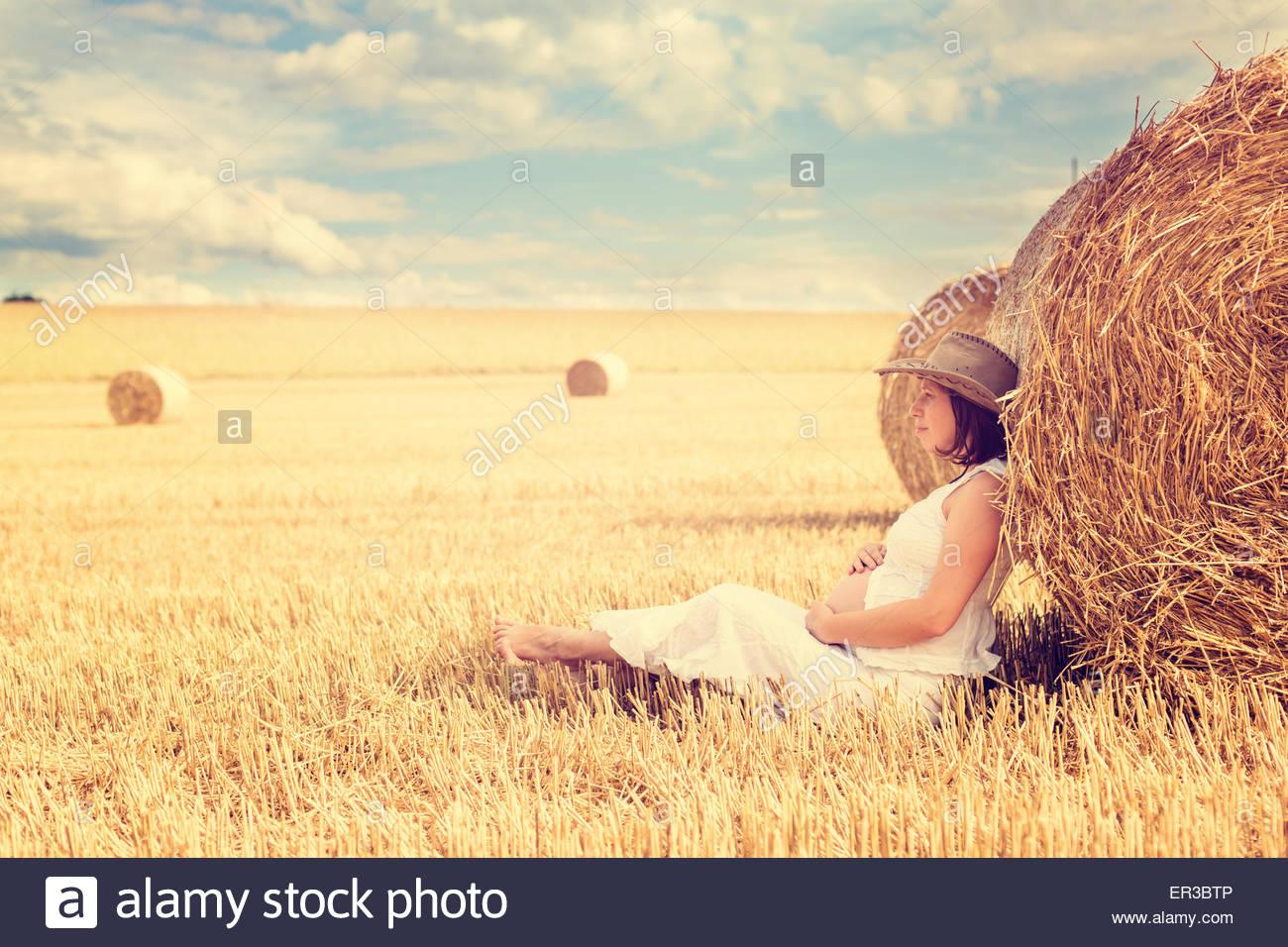 Pregnant woman leaning against a balles de foin dans un champ Photo Stock