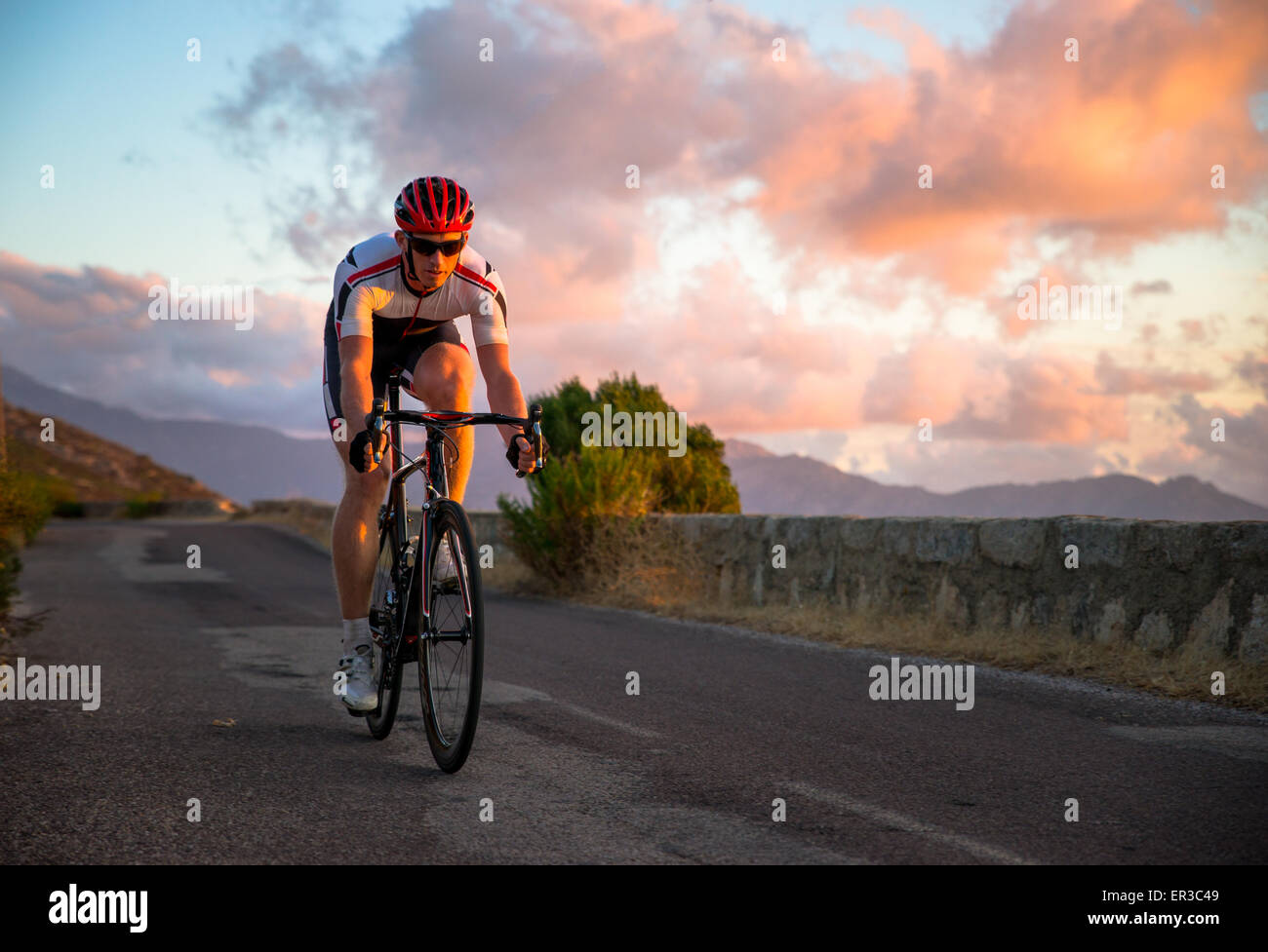 Homme randonnée à vélo au coucher du soleil, Corse, France Photo Stock