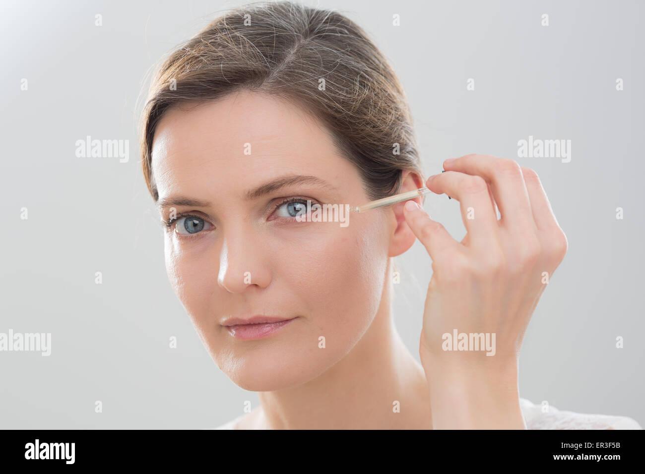 Femme en utilisant le sérum contour des yeux. Photo Stock