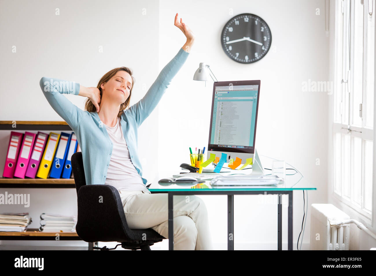 Office woman stretching arms au travail. Photo Stock