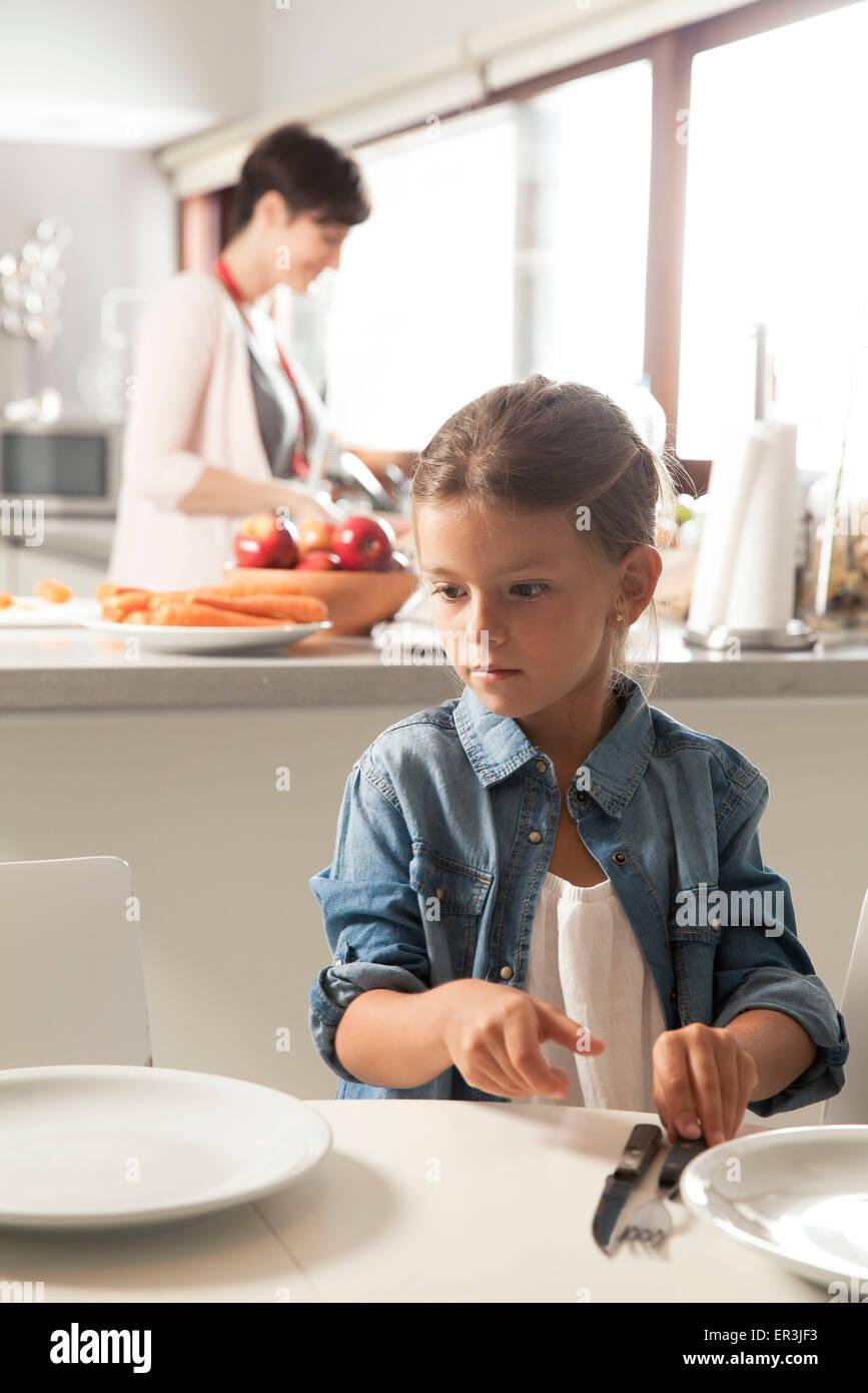 Mettre la table fille, mère de préparer la nourriture dans l'arrière-plan Photo Stock