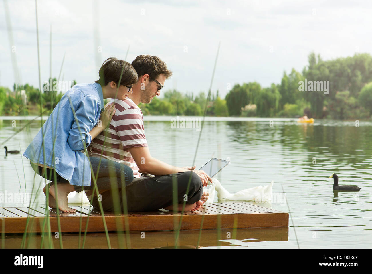 Couple using laptop computer on dock Photo Stock
