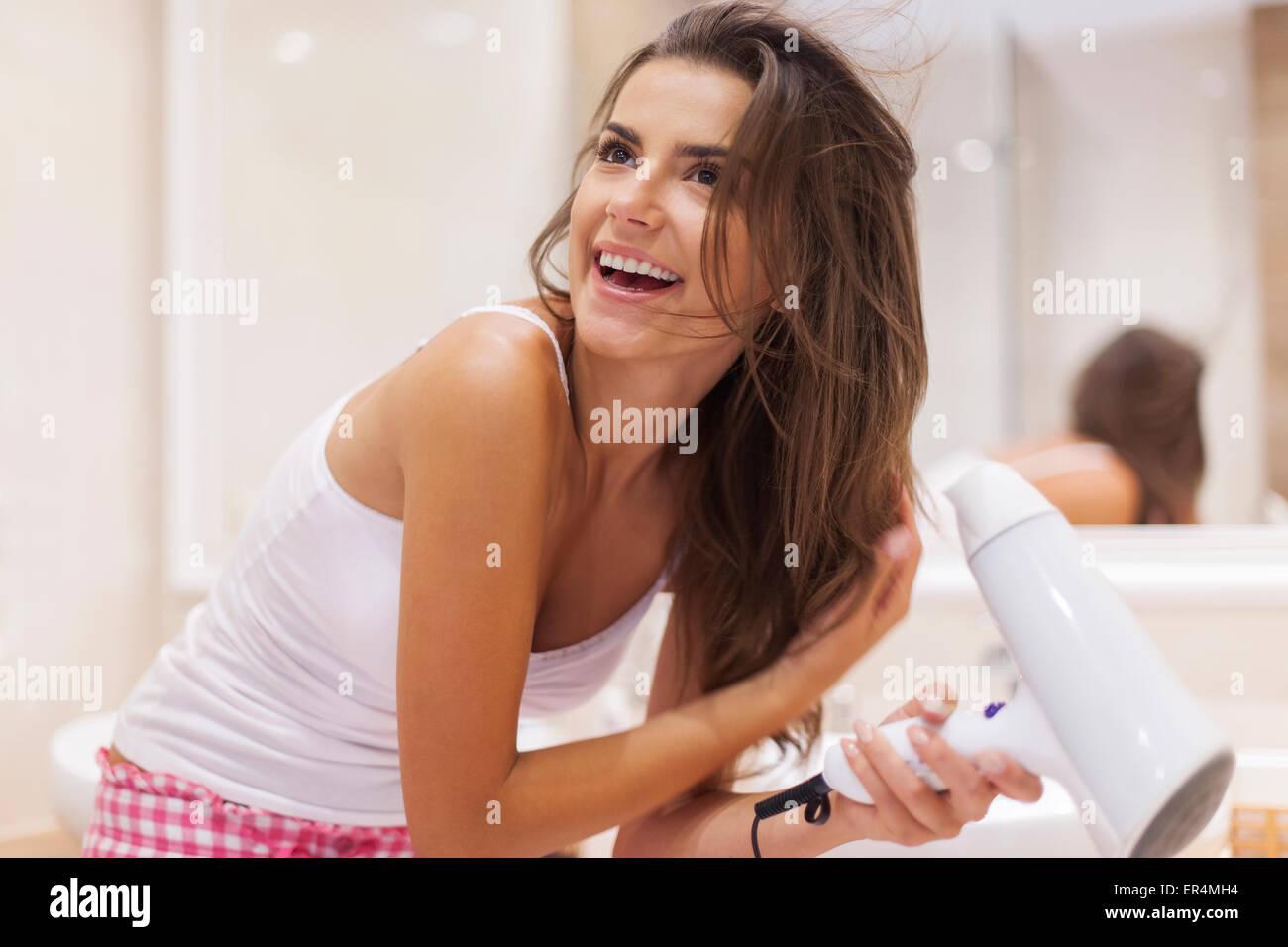 Une jeune femme souffler sécher ses cheveux dans la salle de bains. Debica, Pologne Photo Stock
