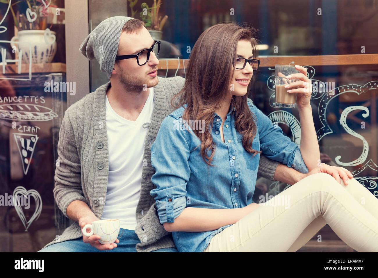 Couple élégant avec tasse de café à l'extérieur du café. Cracovie, Pologne Photo Stock