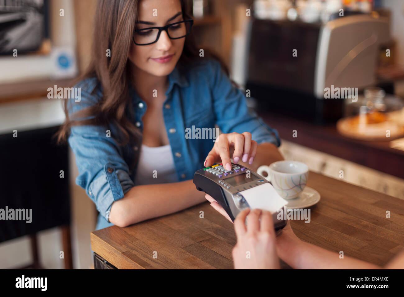 Jeune femme pour payer par carte de crédit cafe reader. Cracovie, Pologne Photo Stock