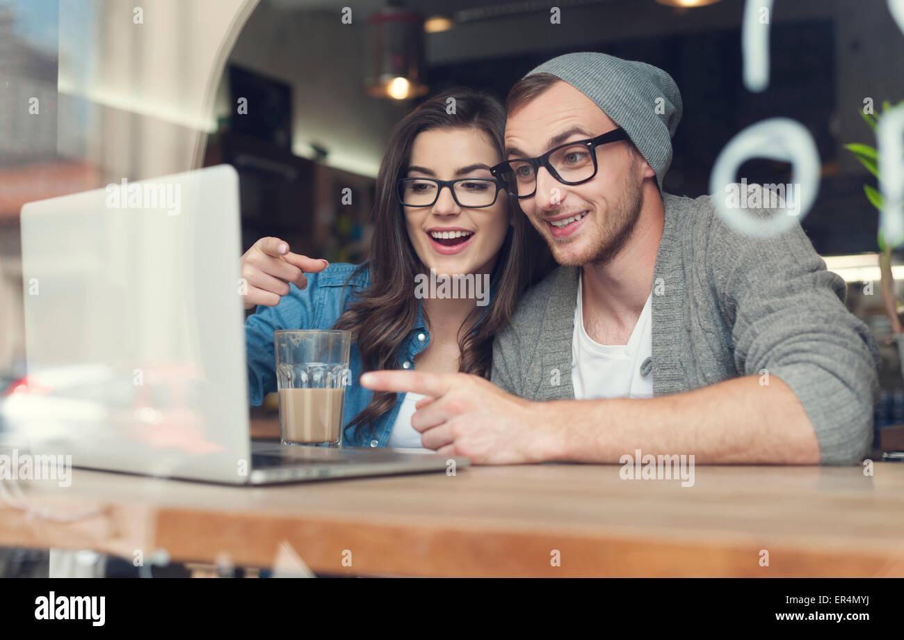 S'amuser en couple à la recherche sur l'ordinateur portable au café. Cracovie, Pologne Photo Stock