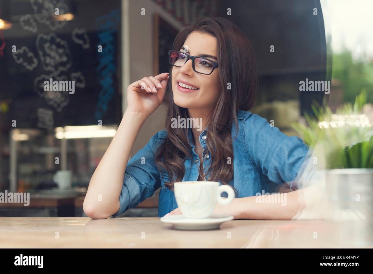 Belle femme portant des lunettes à la mode au café. Cracovie, Pologne Photo Stock
