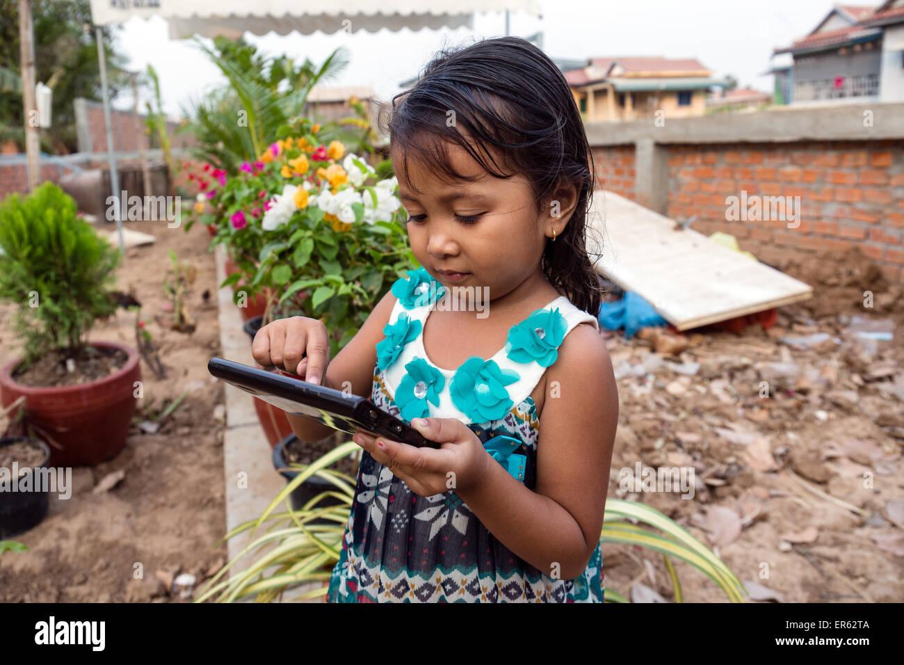 Petite fille jouant avec un ordinateur tablette, Phnom Penh, Cambodge Photo Stock