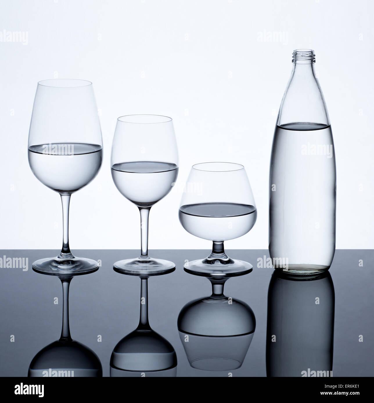 Verrerie et une bouteille remplie d'eau sur fond blanc. Banque D'Images