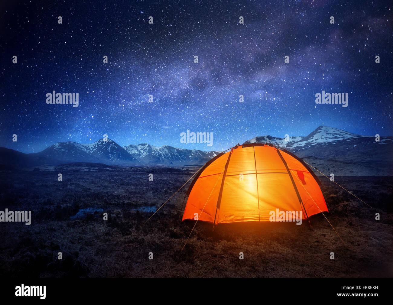 Une tente de camping brille sous un ciel plein d'étoiles. Camping en plein air d'aventure. Photo Stock