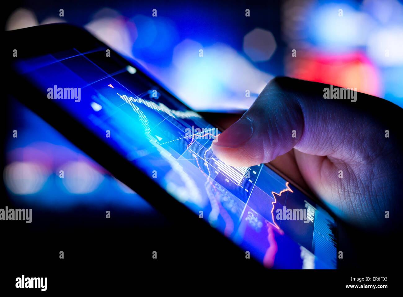 Une personne contrôle les données boursières sur un appareil mobile. Photo Stock