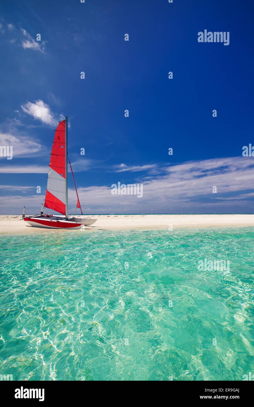 Bateau à voile avec voile rouge sur la plage de l'île tropicale déserte Photo Stock