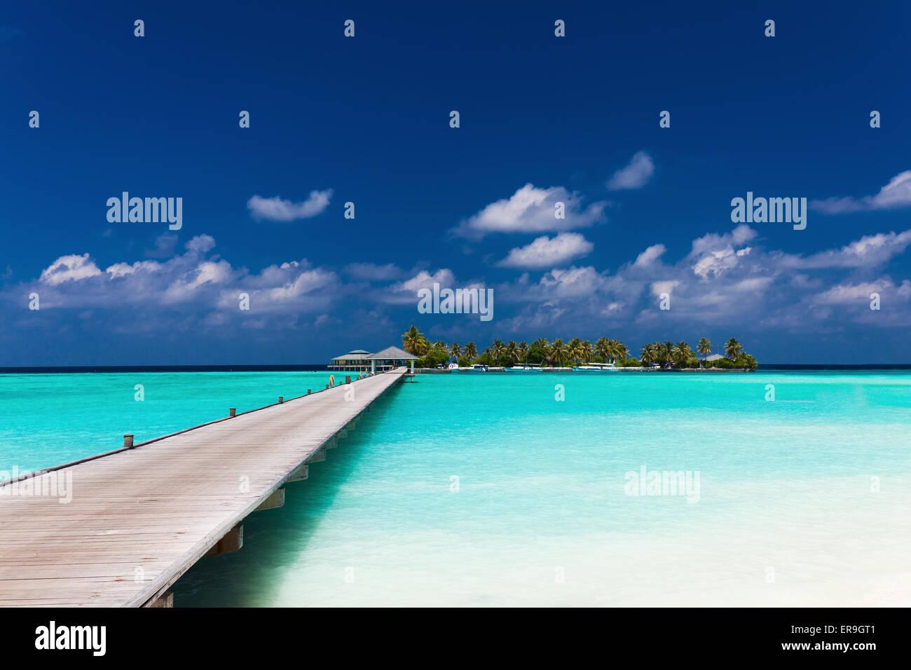 Jetée en bois d'une île tropicale au lagon incroyable aux Maldives Photo Stock