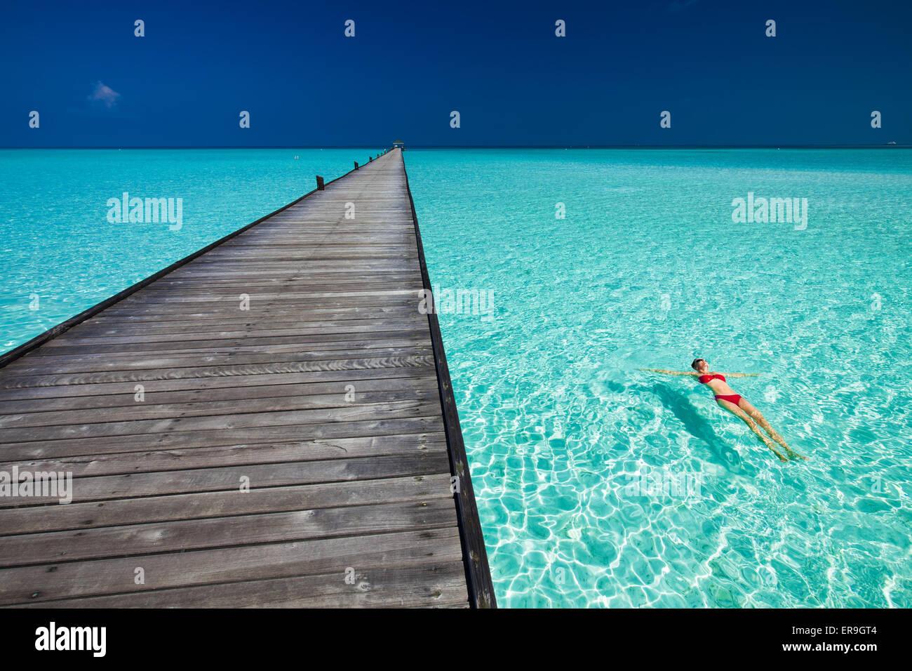 Young woman in red bikini piscine à côté de l'eau jetée dans azure des Maldives Photo Stock