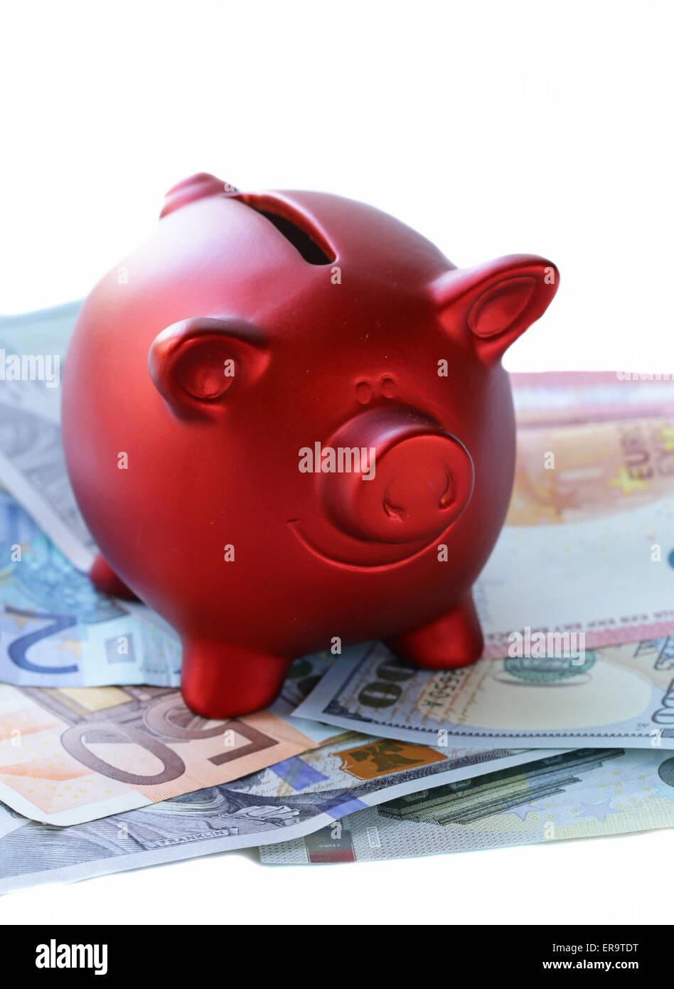 Tirelire rouge avec des billets et des pièces en euros ...