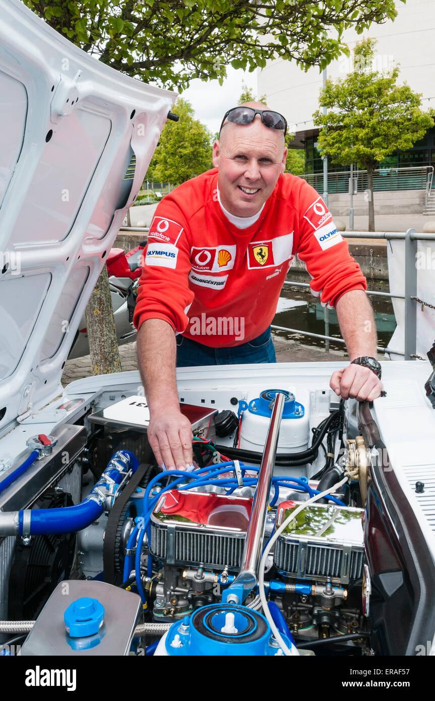 Le propriétaire d'une Fiat 131 rally prêt voiture polit le compartiment moteur. Photo Stock