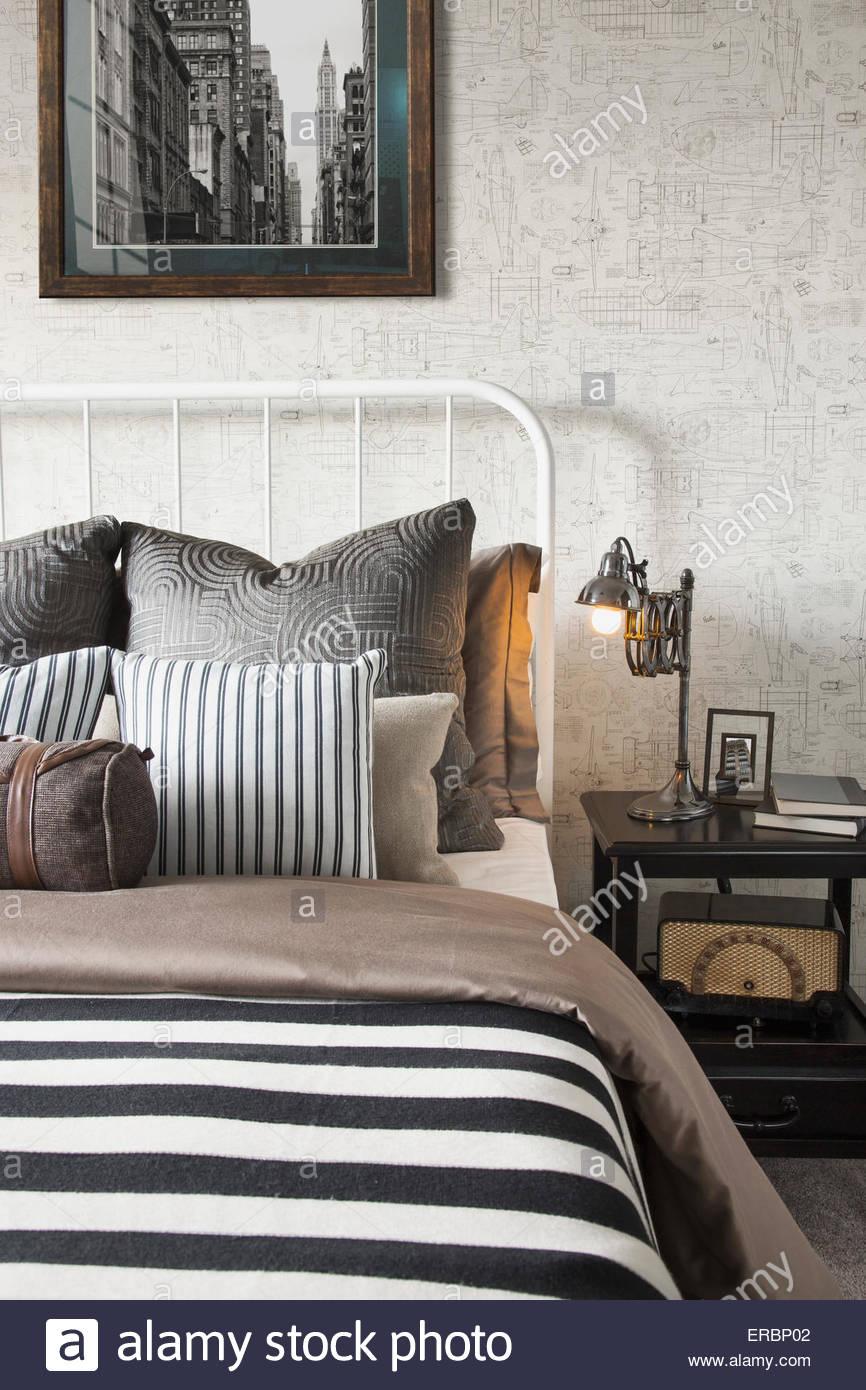 Rayé et oreillers et une couverture à motifs on bed Photo Stock