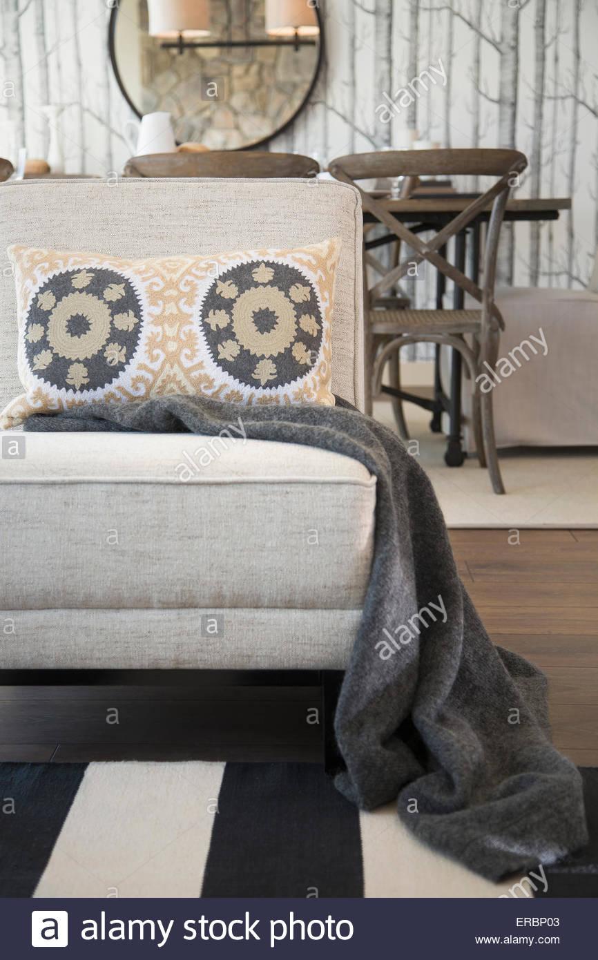 Couverture et oreiller à motifs sur chaise de salon Photo Stock