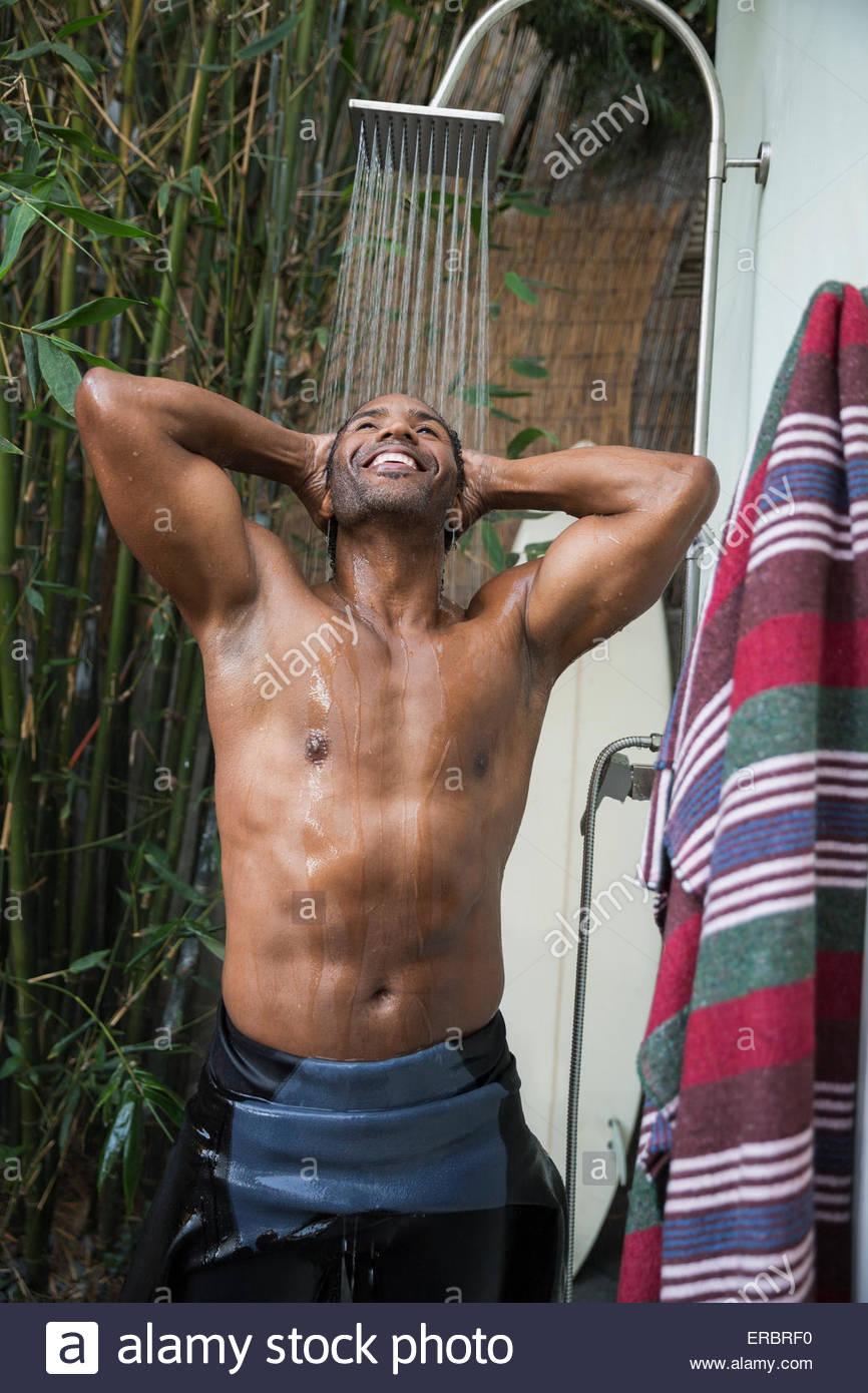 Smiling man in wet suit en utilisant une douche extérieure Photo Stock