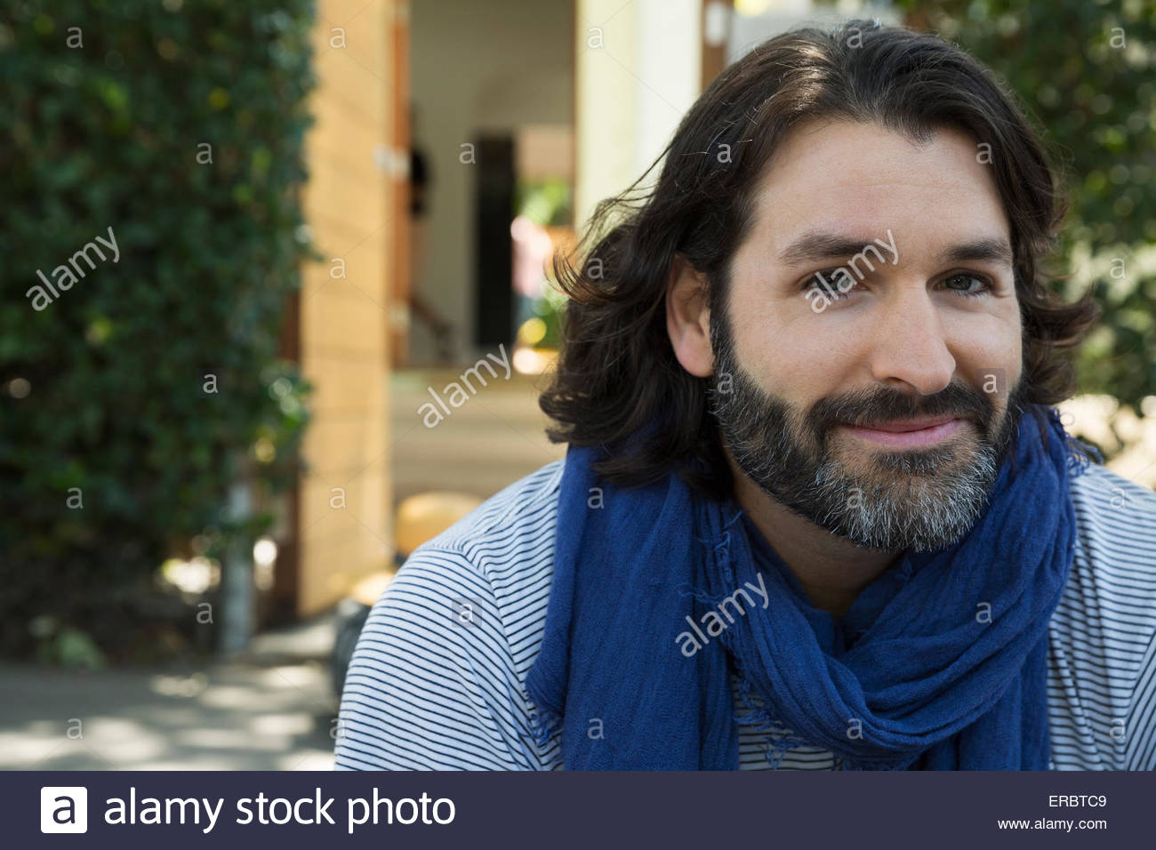 Portrait of smiling man with beard wearing scarf Photo Stock