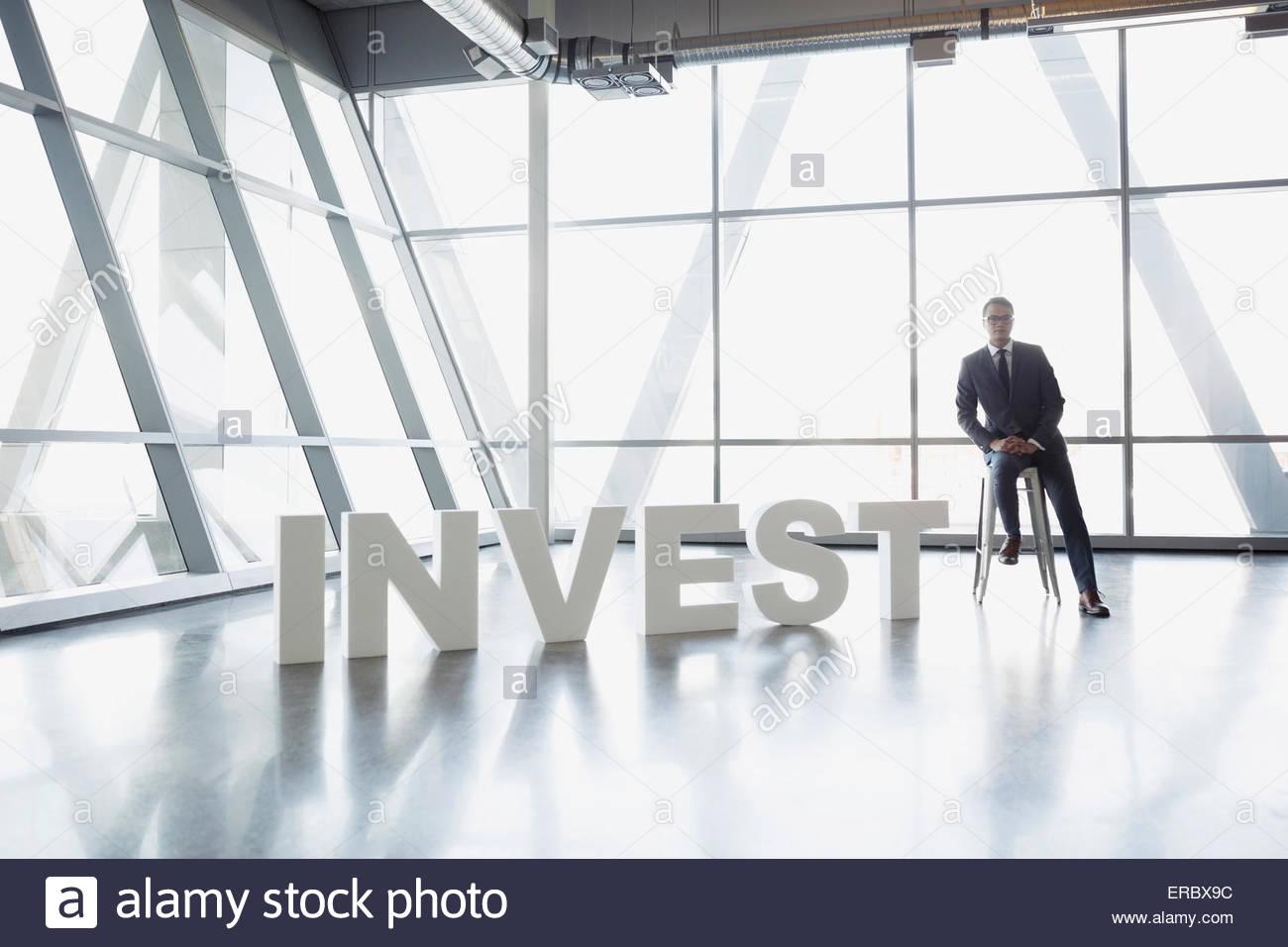 Portrait Portrait à côté de 'Investir' lettres Photo Stock